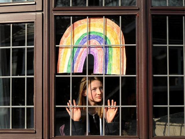 Fleur Hulme pictured with a rainbow in the window of her Leeds home.