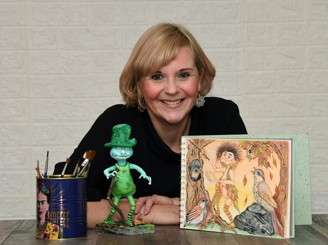 Angela Callard with her illustration for the front cover of her children's book ''The Truth about Itty Bitties' and a model, of an Itty Bitty.