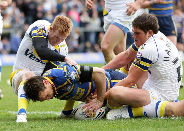 Leeds Rhinos captain Kevin Sinfield goes over for a try as Warrington's Chris Riley (left) and Ben Harrison try and stop him. Picture: Martin Rickett/PA Wire.