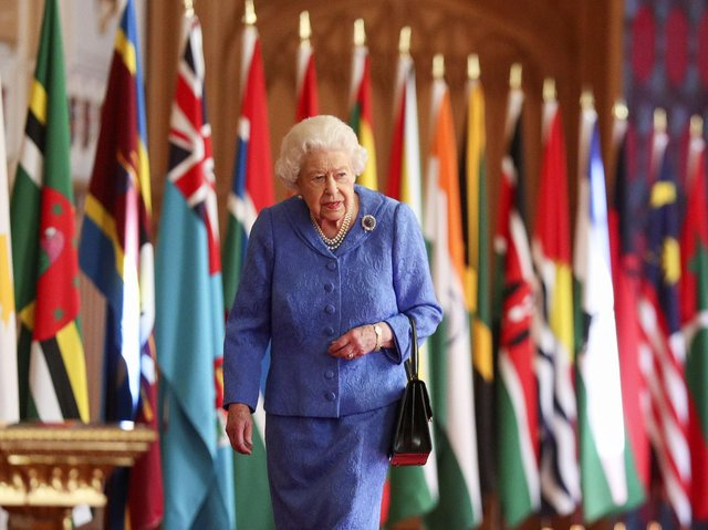 Queen Elizabeth II walks past Commonwealth flags in St George's Hall at Windsor Castle , to mark Commonwealth Day.