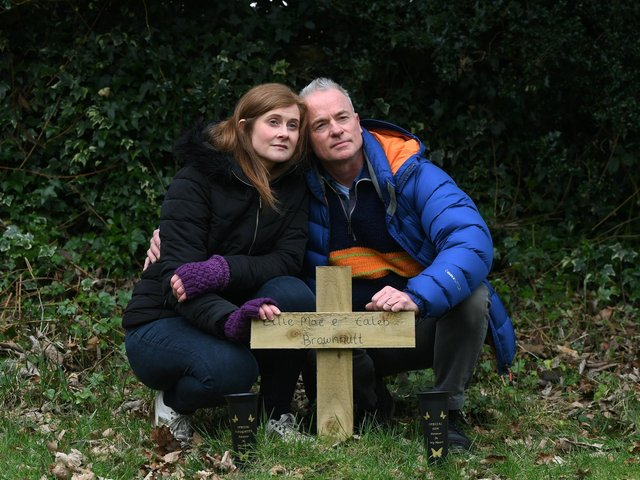 Lynsey Dent and her husband Chris, pictured at the grave of her children Ellie Mae Brownutt and Caleb Brownutt, in the graveyard of St Chad's Parish Church in Headingley. Picture : Jonathan Gawthorpe