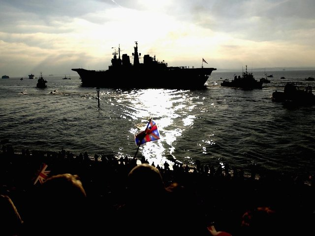 PORTSMOUTH, ENGLAND - Members of the public line the shore as the aircraft carrier HMS Ark Royal leaves her base in Portsmouth to lead a Naval Task Group to the Mediterranean. (Photo by Julian Herbert/Getty Images)