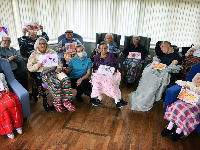 Residents at Moorleigh Nursing Home in Kippax with drawings by children at Little Learners Nursery. Residents are pictured with activities coordinator Oona-mai Sharp. Picture : Jonathan Gawthorpe