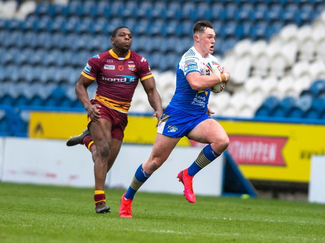 Jack Broadbent held off Jermaine McGillvary to score a long-range try for Rhinos at Huddersfield. Picture by Tony Johnson.