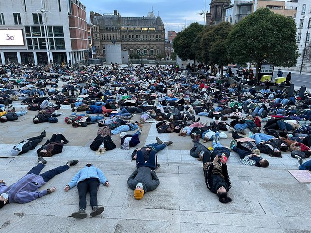Hundreds lay on the ground at Millennium Square on Monday evening at a vigil for Sarah Everard