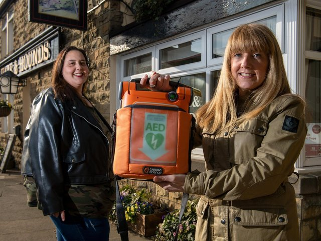 Louisa Pouncett, WF3 Kindness Volunteer, and Camille Leach, secretary for West Ardsley Action Group with the defibrillator at the Hare and Hounds in West Ardsley. Picture: Bruce Rollinson