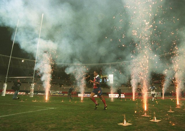 Paris St Germain and Sheffield Eagles players run through a tunnel of fireworks and enter the pitch for the start of Super League at Stade Charetly in March, 1996. Picture: Matthew Ashton/PA.