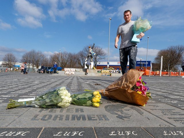 A man lays a floral tribute outside Elland Road in Leeds, following the death of Leeds' all-time record goalscorer Peter Lorimer (Photo: Danny Lawson/PA Wire)