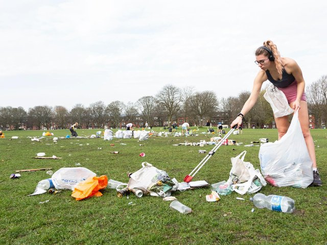 A woman helps to clear away rubbish on Woodhouse Moor (photo: SWNS).
