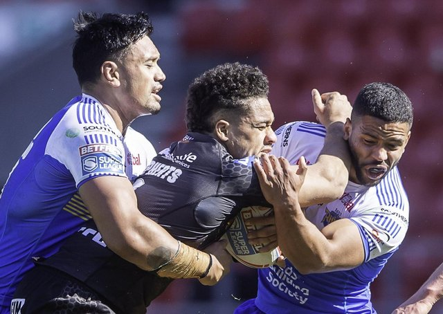 BIG HITTER: Castleford's Derrell Olpherts is tackled by Leeds Rhinos' Zane Tetevano, left, and Kruise Leeming. Picture: Allan McKenzie/SWpix.com.
