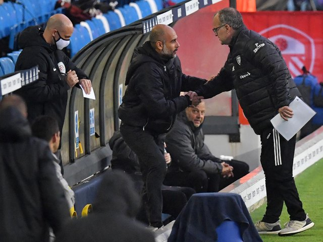 MEETING OF MINDS: Leeds United head coach Marcelo Bielsa, right, greets Manchester City boss Pep Guardiola, centre, before October's clash at Elland Road. Photo by PAUL ELLIS/POOL/AFP via Getty Images.