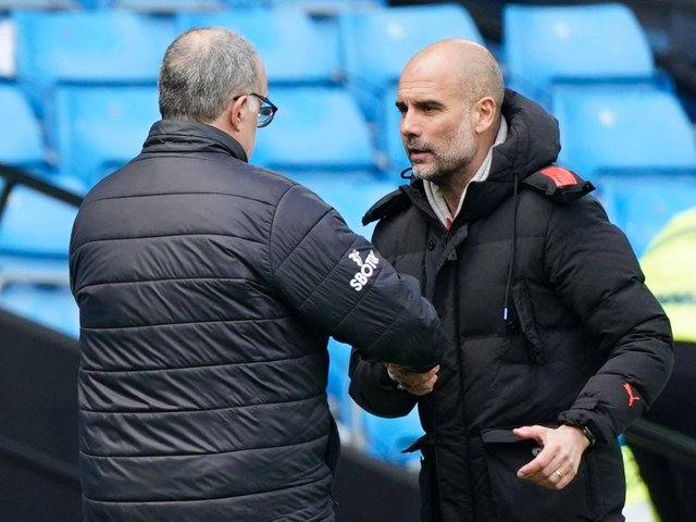 PRAISE: From Manchester City boss Pep Guardiola, right, pictured embracing Leeds United head coach Marcelo Bielsa after Saturday's clash at the Etihad. Photo by TIM KEETON/POOL/AFP via Getty Images.