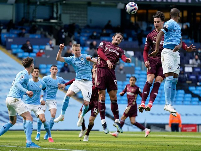 GRINDING IT OUT: Leeds United defenders Pascal Struijk, left, and Robin Koch, right, look to clear as Manchester City produce another attack in Saturday's clash at the Etihad. Photo by TIM KEETON/POOL/AFP via Getty Images.