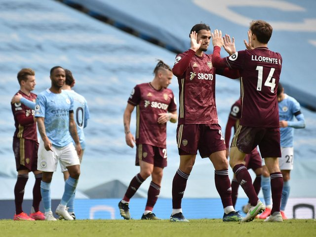 JOB DONE: Diego Llorente, right, and Pascal Struijk, second right, high five after Leeds United's 2-1 victory at runaway leaders Manchester City as England star Raheem Sterling, second left, looks on. Photo by RUI VIEIRA/POOL/AFP via Getty Images.