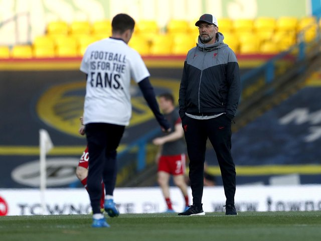 Liverpool manager Jurgen Klopp looks on as a Leeds United player warms up on the pitch wearing a shirt opposing the new European Super League ahead of the Premier League match at Elland Road