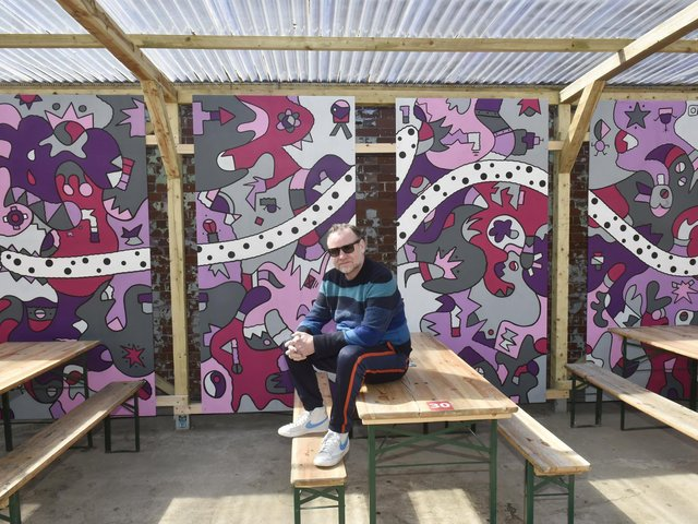 Street artist Nicolas Dixon with his new mural at Chow Down festival