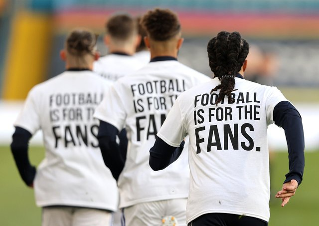 Leeds United players wearing 'Football Is For The Fans' shirts during the warm up prior to kick-off during the Premier League match agaimnst Liverpool (Picture: PA)