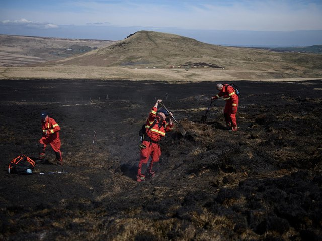 Firefighters tackle any resurgence of a moor fire on Marsden Moor