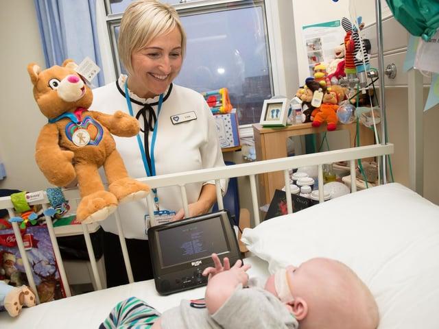 Lisa from Leeds Congenital Heart Unit handing out a Katie bear teddy to baby Oscar.