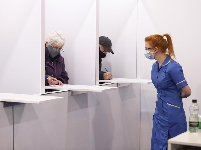 Members of the public fill out paperwork before being given the coronavirus vaccine at the Elland Road  (photo: PA Wire/ Danny Lawson)