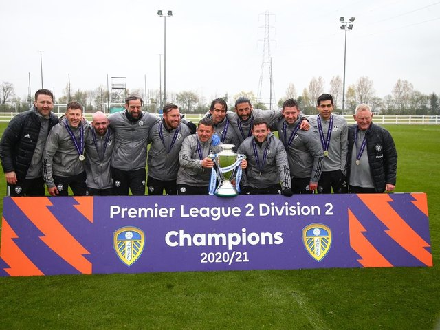 CHAMPIONS RAIN: Mark Jackson and his team of coaches get their hands on the Premier League Two Division Two trophy after a completing a stunning season with Leeds United's under-23s. Picture by LUFC.