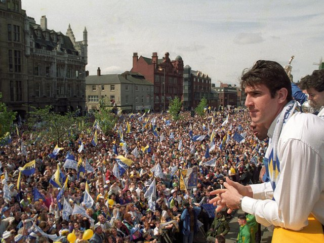Eric Cantona looks out onto a sea of fans during a civic reception for Leeds United after winning the First Division title.