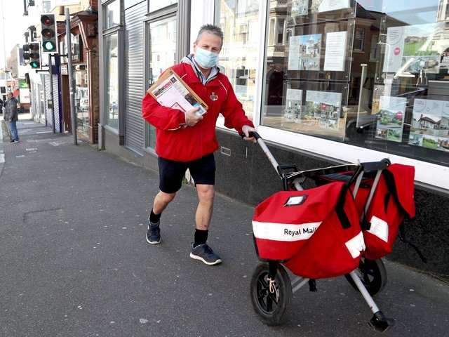 File photo of a postman wearing a mask and gloves to deliver letters in Broadstairs, Kent.