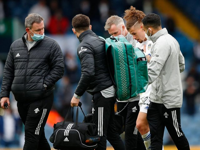 CONCERN: As Kalvin Phillips is helped off the Elland Road pitch. Photo by LYNNE CAMERON/POOL/AFP via Getty Images.