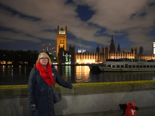 Mo Lea, 61, from Bedford, standing in front of her animation of Lady Justice being projected onto the Houses of Parliament