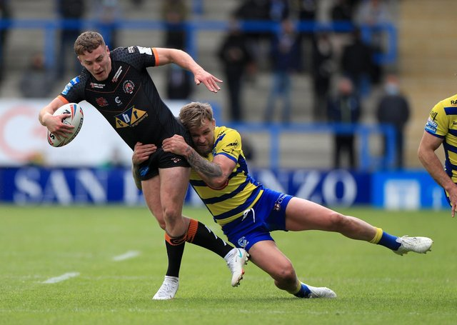 HELD BACK: Castleford Tigers' Jacob Trueman (left) is tackled by Warrington Wolves' Blake Austin at the Halliwell Jones Stadium. Picture: Mike Egerton/PA
