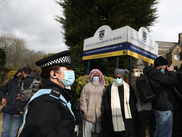 A police officer observes protesters gathered outside Batley Grammar School in Batley, West Yorkshire, where a teacher was suspended for reportedly showing a caricature of the Prophet Mohammed to pupils during a religious studies lesson in March. Photo credit:  Danny Lawson/PA Wire