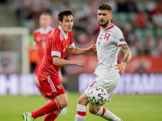 ARCHITECT: Leeds United's Mateusz Klich, right, in Poland's 1-1 draw against Russia, pictured as the Whites midfielder locks horns with Vyacheslav Karavaev. Photo by Thomas Eisenhuth/Getty Images.