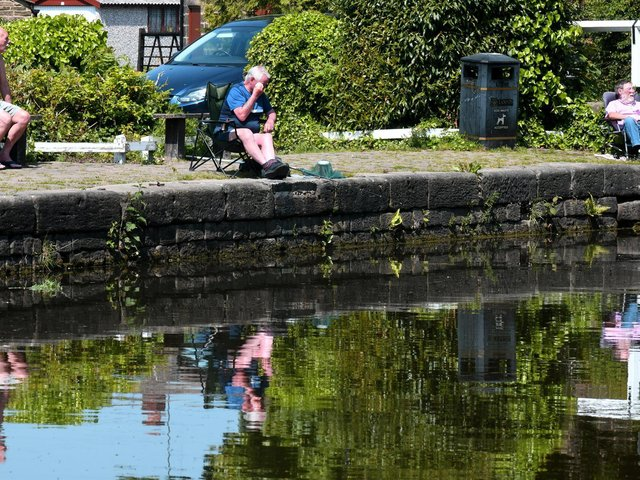 Fishermen are reflected in the Leeds Liverpool Canal at Rodley in the sun