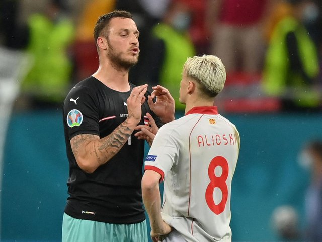 APOLOGY ISSUED - Marko Arnautovic speaks with North Macedonia and Leeds United defender Ezgjan Alioski at the end of the UEFA EURO 2020 Group C match. Pic: Getty