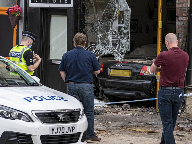 A police cordon is in place after a car crashed through a window in Stanningley.