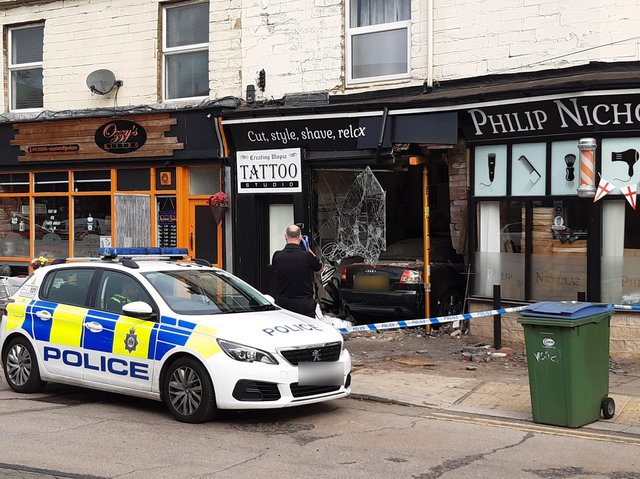 A man has been arrested after a car crashed through a window in Bradford Road.