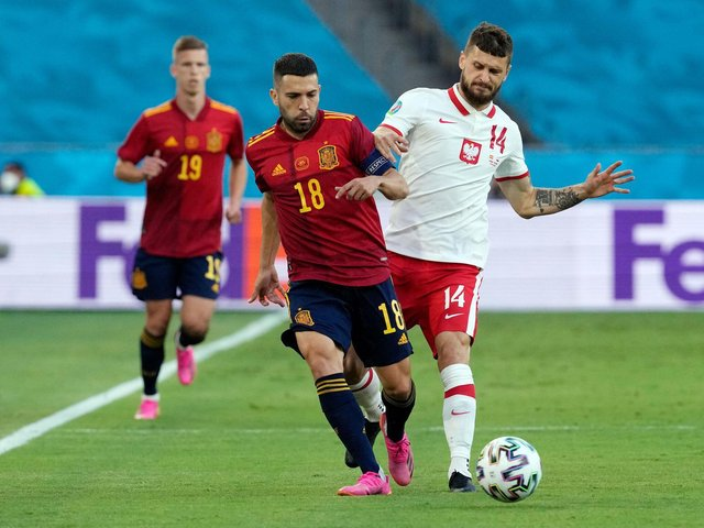 STILL IN IT: Leeds United midfielder Mateusz Klich, right, battles it out with Spain's Jordi Alba in Saturday's 1-1 draw in Seville. Photo by THANASSIS STAVRAKIS/POOL/AFP via Getty Images.