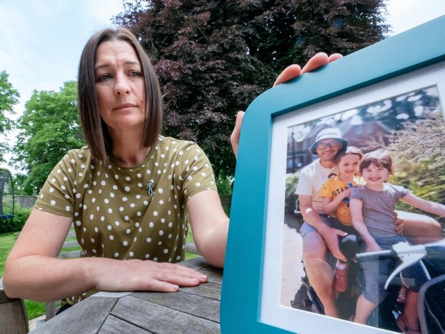 Tina Pinder, with a photo of her late husband Lloyd Pinder and their two children Gracie (second right), 12 and Lola (right), 8, at her home in South Milford, North Yorkshire (photo: PA Wire/ Danny Lawson)