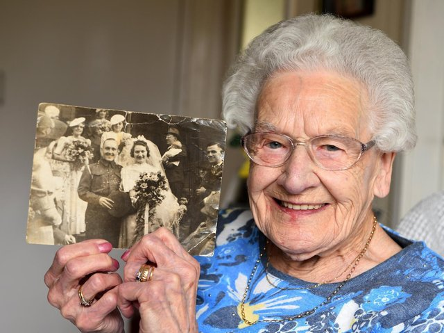 Centenarian Constance Stead holding a photo of her and late husband Wilfred on their wedding day on September 27 1941.