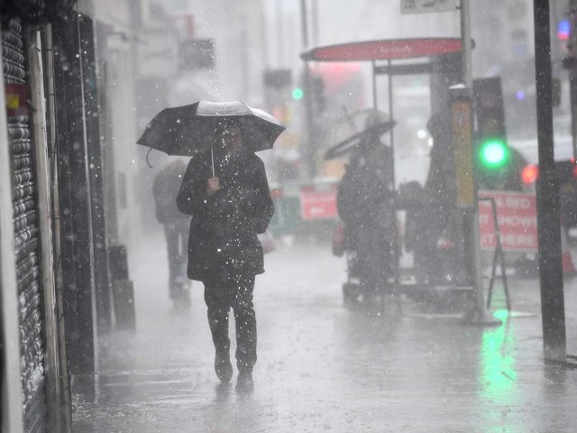 A man walking in a rain shower in east London. Picture date: Tuesday July 6, 2021.