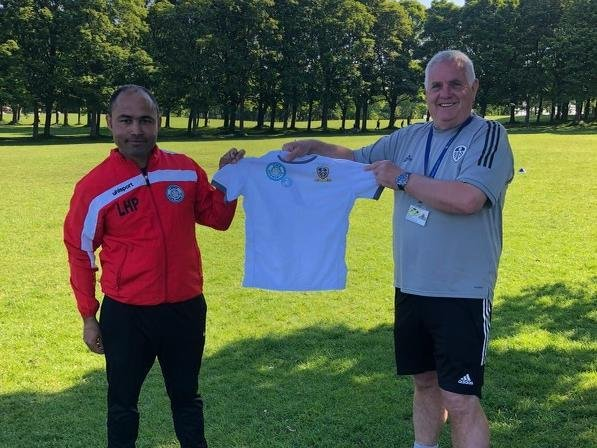 Adel Chermiti, founder of Leeds Hyde Park FC receiving new kit from Terry Porter, of Leeds United Academy.
