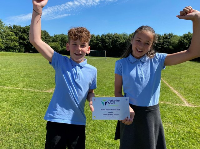 Year 5 pupils, Lewis and Ava hold the plaque the school was presented with for its achievement.