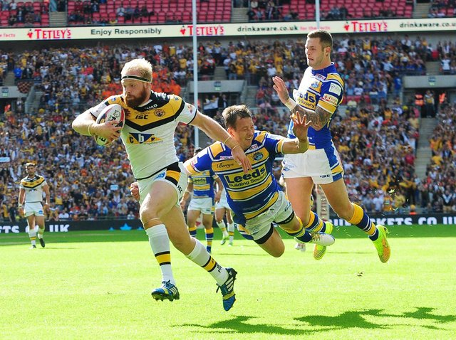 Oliver Holmes gets past Danny McGuire and Zak Hardaker to score for Tigers against Leeds at Wembley in 2014. Picture by Steve Riding.