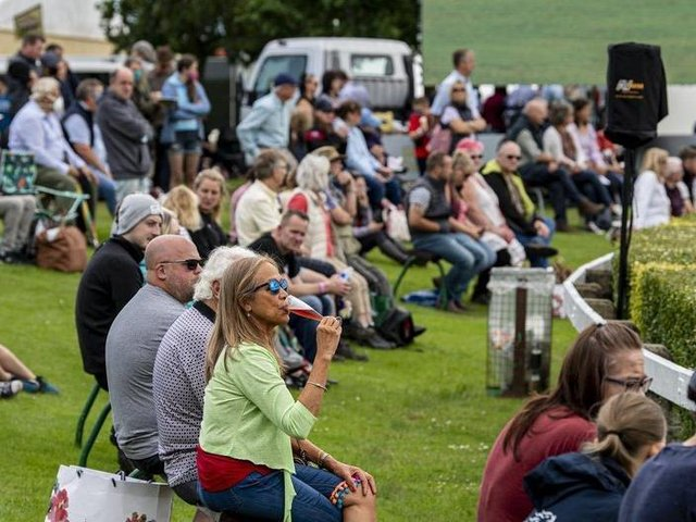 Visitors to the first day of the show relax in the fine weather to watch the showjumping in the main ring. Picture Tony Johnson.