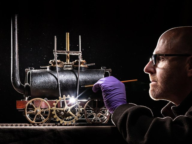 John McGoldrick, curator of industrial history at the Leeds Industrial Museum, cleans the world's oldest model locomotive as it returns to the attraction.  PIC: Danny Lawson / PA