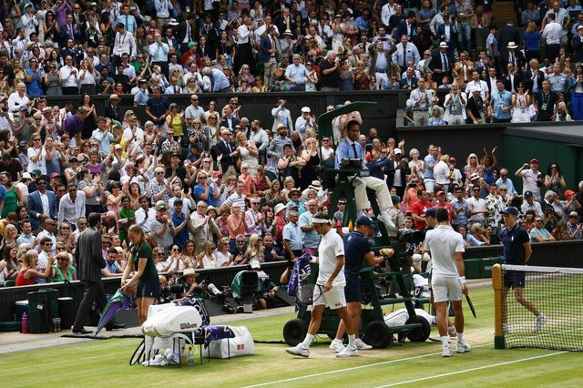 The Wimbledon crowd stand and applaud at the end of a game as Switzerland's Roger Federer and Serbia's Novak Djokovic take their seats during the men's singles final on day in 2019. (Pic: Getty Images)