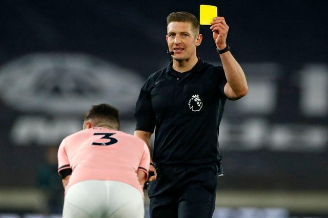 English referee Robert Jones shows a yellow card to Sheffield United's Irish defender Enda Stevens. (Photo by JASON CAIRNDUFF/POOL/AFP via Getty Images)